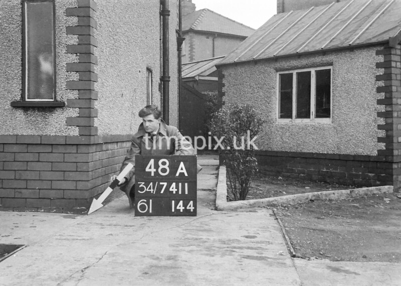 SD741148A, Man marking Ordnance Survey minor control revision point with an arrow in 1940s