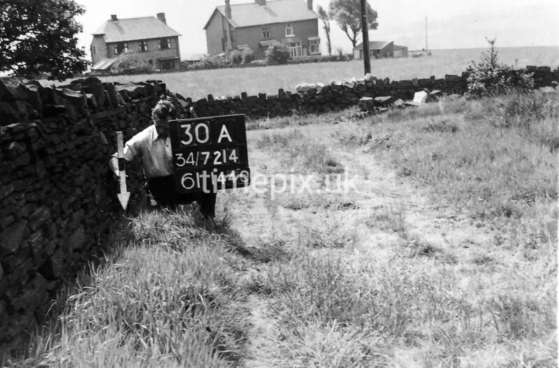 SD721430A, Man marking Ordnance Survey minor control revision point with an arrow in 1950s