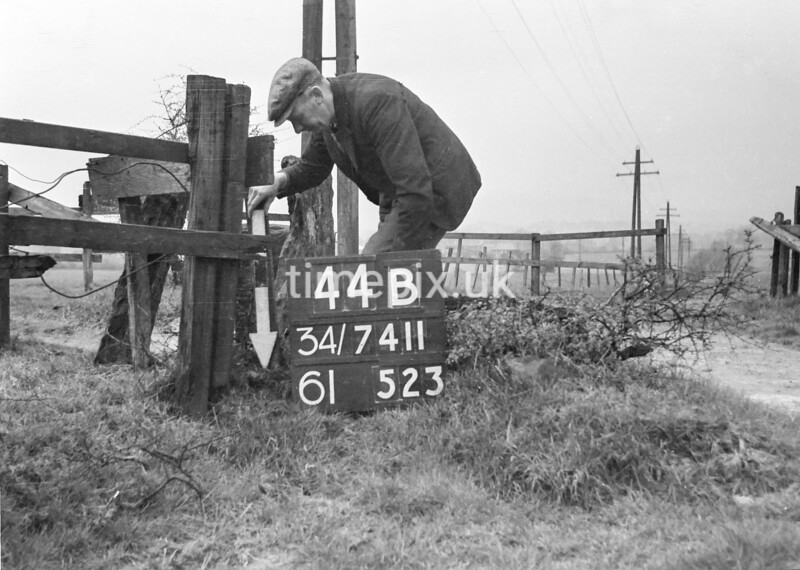 SD741144B, Man marking Ordnance Survey minor control revision point with an arrow in 1940s