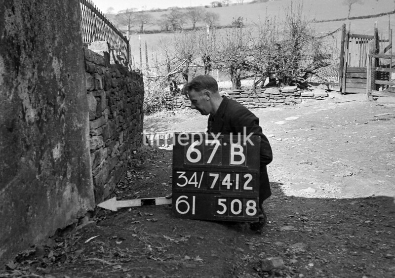 SD741267B, Man marking Ordnance Survey minor control revision point with an arrow in 1950s
