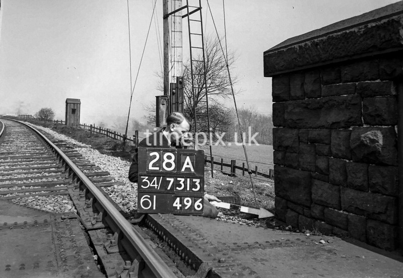 SD731328A, Man marking Ordnance Survey minor control revision point with an arrow in 1940s