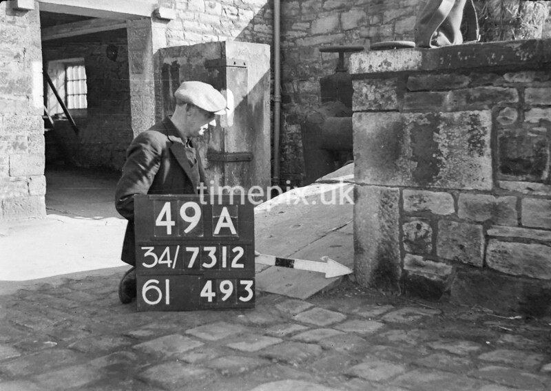 SD731249A2, Man marking Ordnance Survey minor control revision point with an arrow in 1940s
