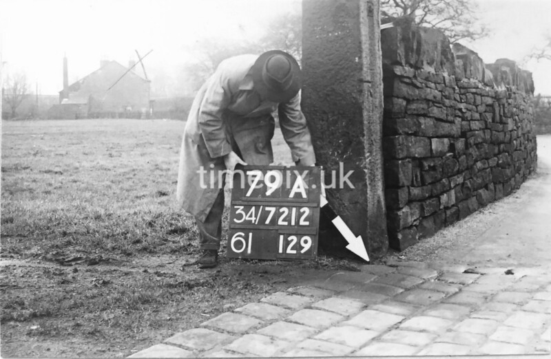 SD721279A, Man marking Ordnance Survey minor control revision point with an arrow in 1940s