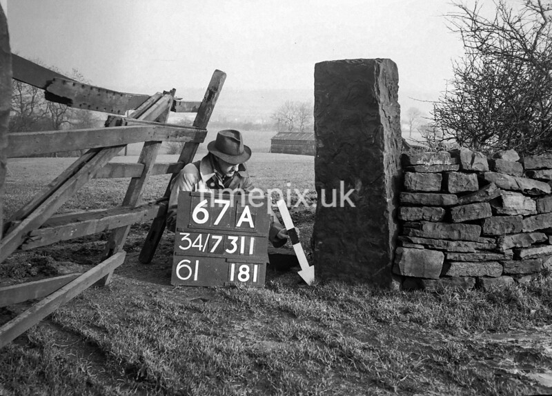 SD731167A, Man marking Ordnance Survey minor control revision point with an arrow in 1940s