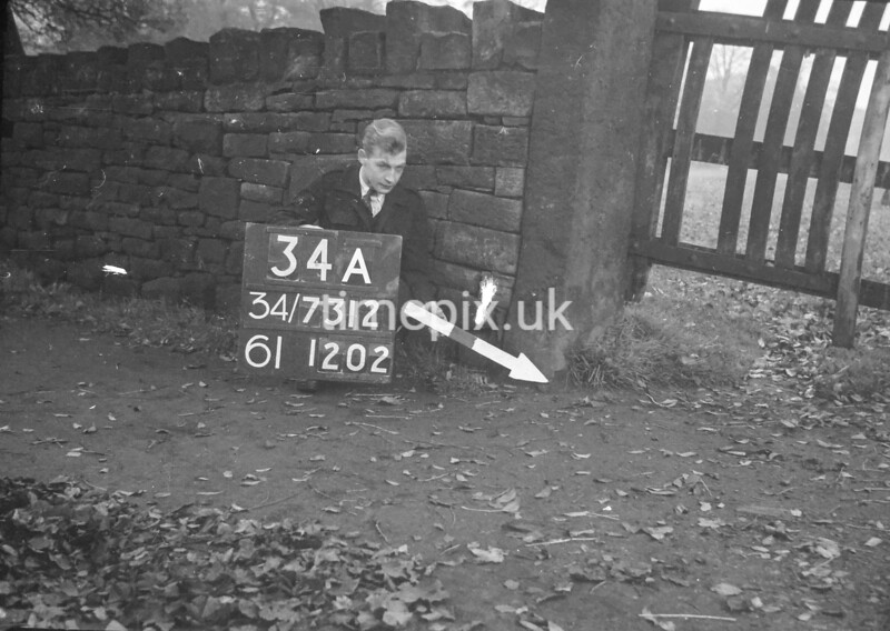 SD731234A, Man marking Ordnance Survey minor control revision point with an arrow in 1940s