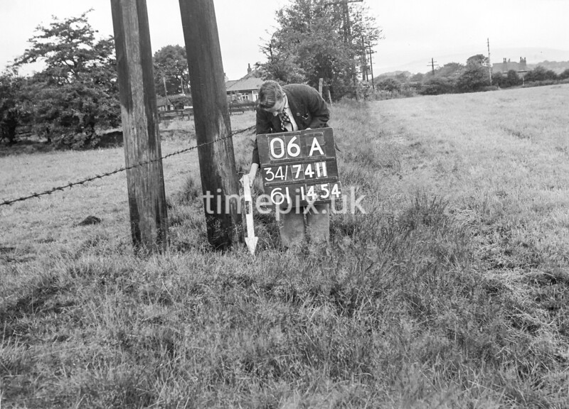 SD741106A, Man marking Ordnance Survey minor control revision point with an arrow in 1950s