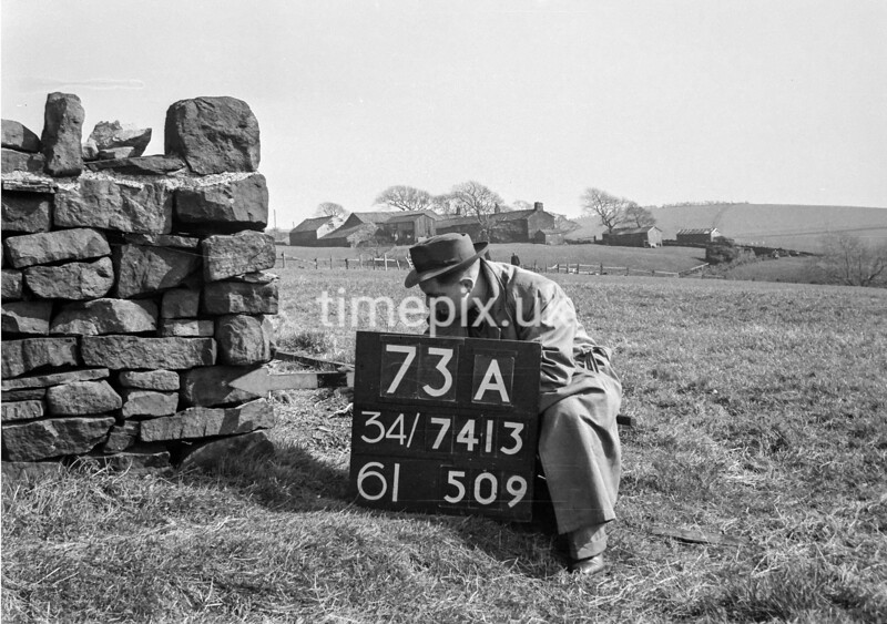 SD741373A, Man marking Ordnance Survey minor control revision point with an arrow in 1950s
