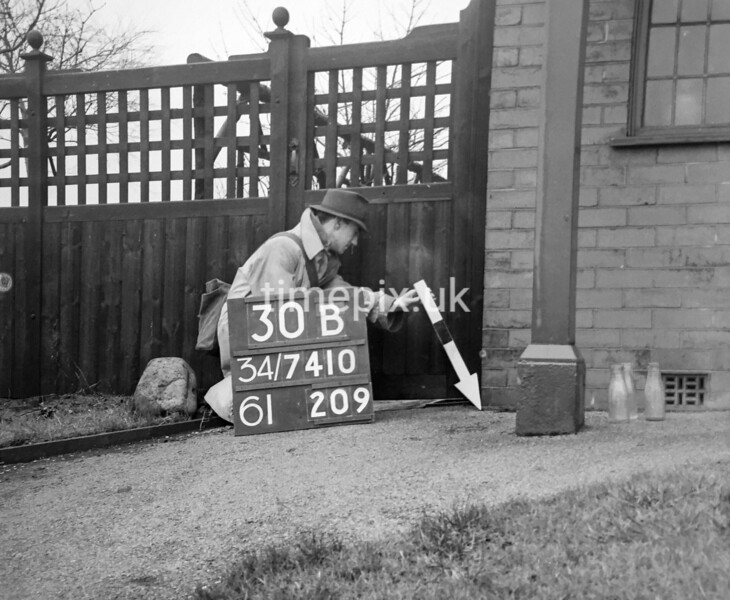 SD741030B, Man marking Ordnance Survey minor control revision point with an arrow in 1940s