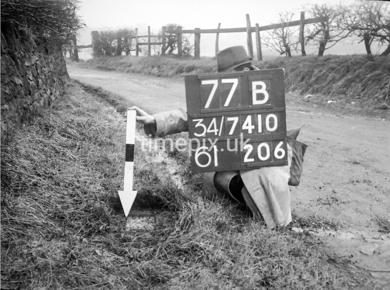 SD741077B, Man marking Ordnance Survey minor control revision point with an arrow in 1940s