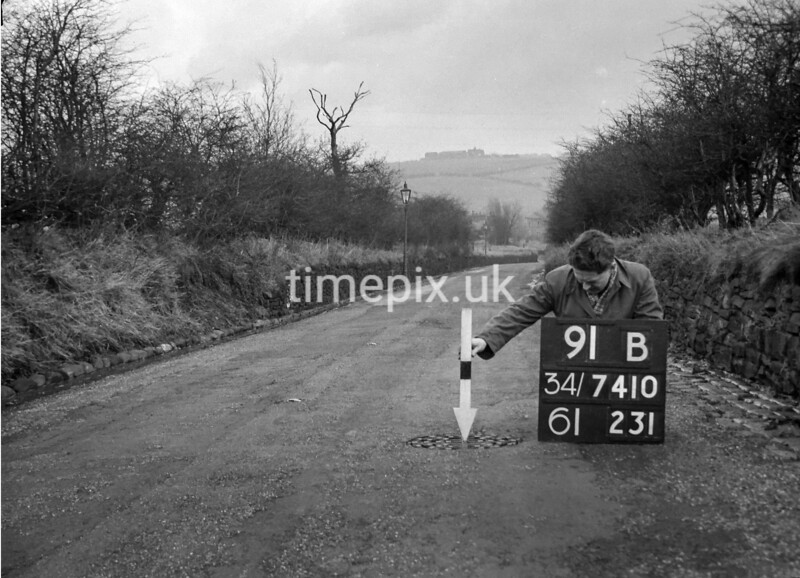 SD741091B, Man marking Ordnance Survey minor control revision point with an arrow in 1940s