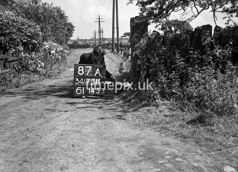 SD731187A, Man marking Ordnance Survey minor control revision point with an arrow in 1950s