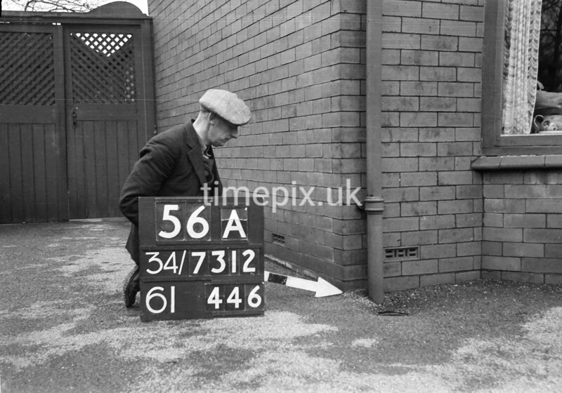 SD731256A, Man marking Ordnance Survey minor control revision point with an arrow in 1940s