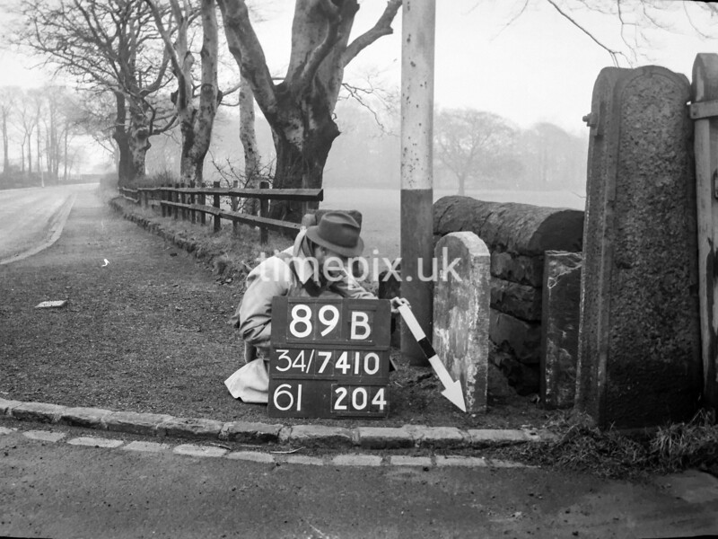 SD741089B, Man marking Ordnance Survey minor control revision point with an arrow in 1940s