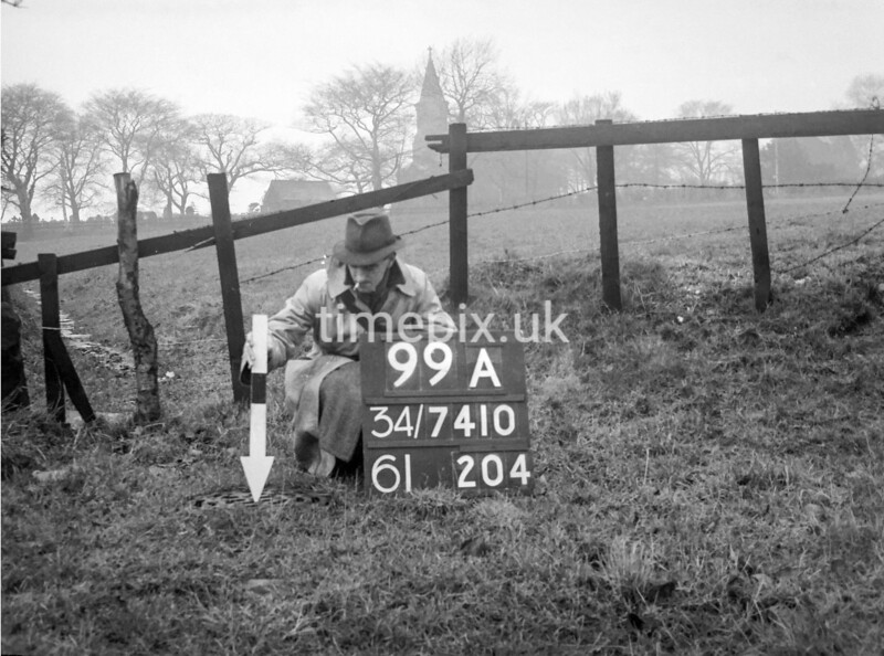 SD741099A, Man marking Ordnance Survey minor control revision point with an arrow in 1940s