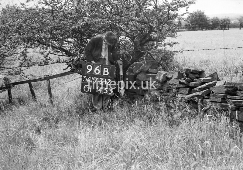 SD731296B, Man marking Ordnance Survey minor control revision point with an arrow in 1950s
