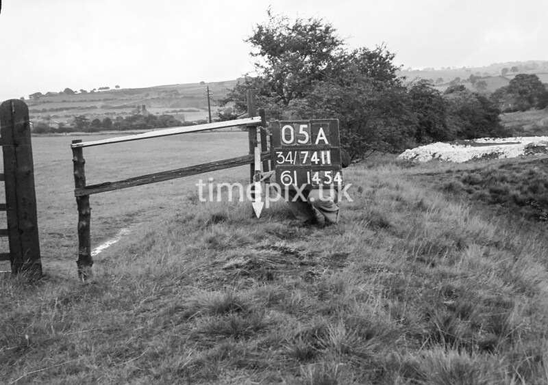 SD741105A, Man marking Ordnance Survey minor control revision point with an arrow in 1950s