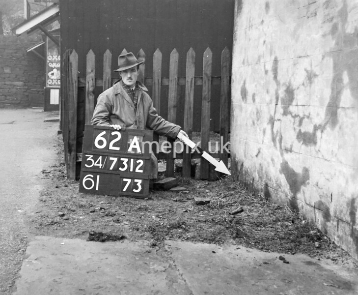 SD731262A, Man marking Ordnance Survey minor control revision point with an arrow in 1940s