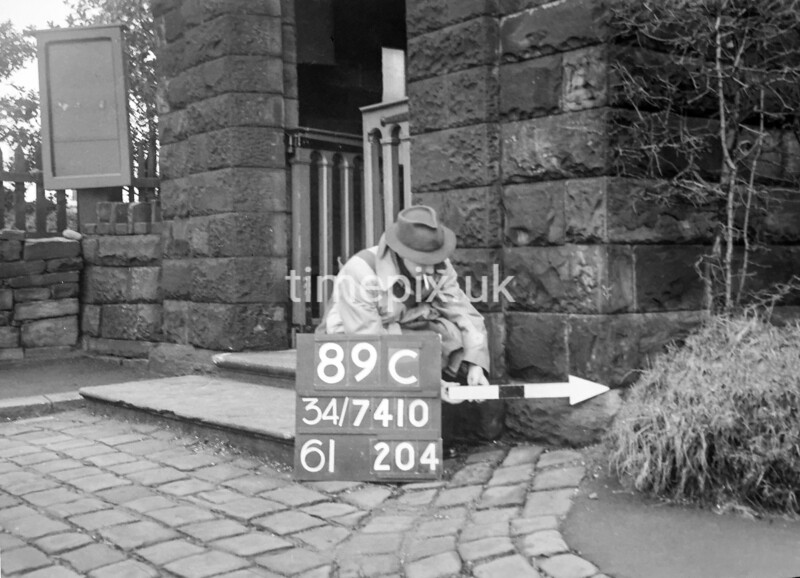 SD741089C, Man marking Ordnance Survey minor control revision point with an arrow in 1940s
