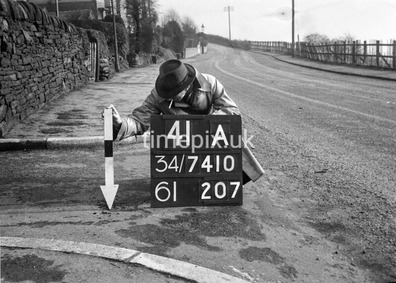 SD741041A, Man marking Ordnance Survey minor control revision point with an arrow in 1940s