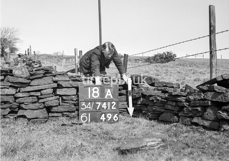 SD741218A, Man marking Ordnance Survey minor control revision point with an arrow in 1950s