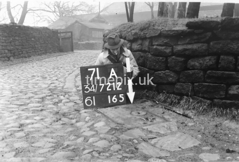 SD721271A, Man marking Ordnance Survey minor control revision point with an arrow in 1940s
