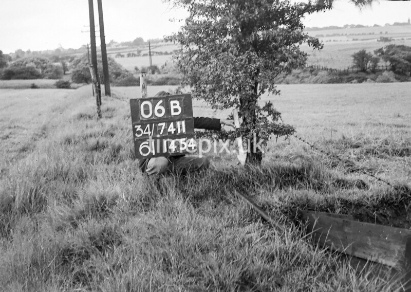 SD741106B, Man marking Ordnance Survey minor control revision point with an arrow in 1950s