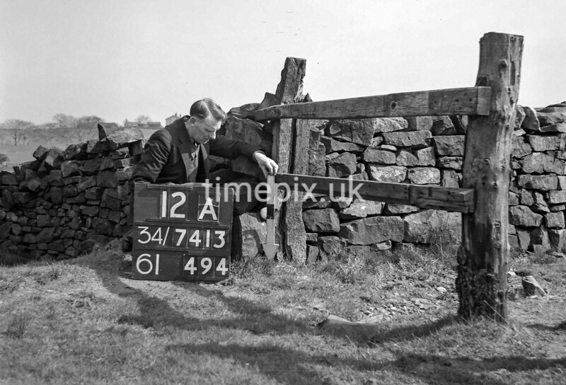 SD731312A, Man marking Ordnance Survey minor control revision point with an arrow in 1940s