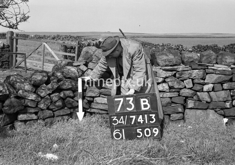 SD741373B, Man marking Ordnance Survey minor control revision point with an arrow in 1950s