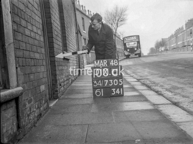 SD730500C, Man marking Ordnance Survey minor control revision point with an arrow in 1940s