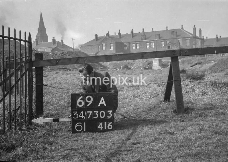 SD730369A, Man marking Ordnance Survey minor control revision point with an arrow in 1940s