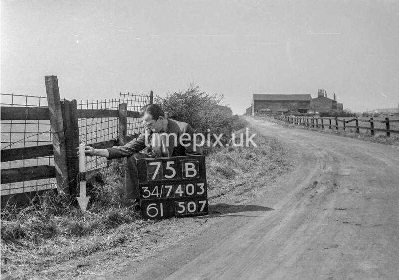 SD740375B, Man marking Ordnance Survey minor control revision point with an arrow in 1940s