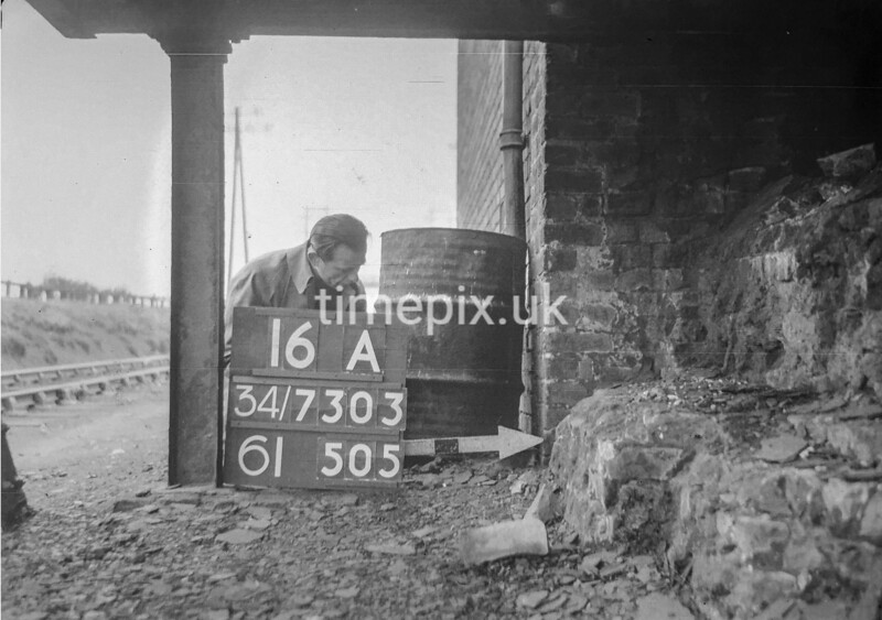 SD730316A, Man marking Ordnance Survey minor control revision point with an arrow in 1940s