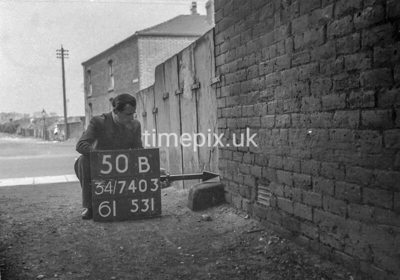 SD740350B, Man marking Ordnance Survey minor control revision point with an arrow in 1940s