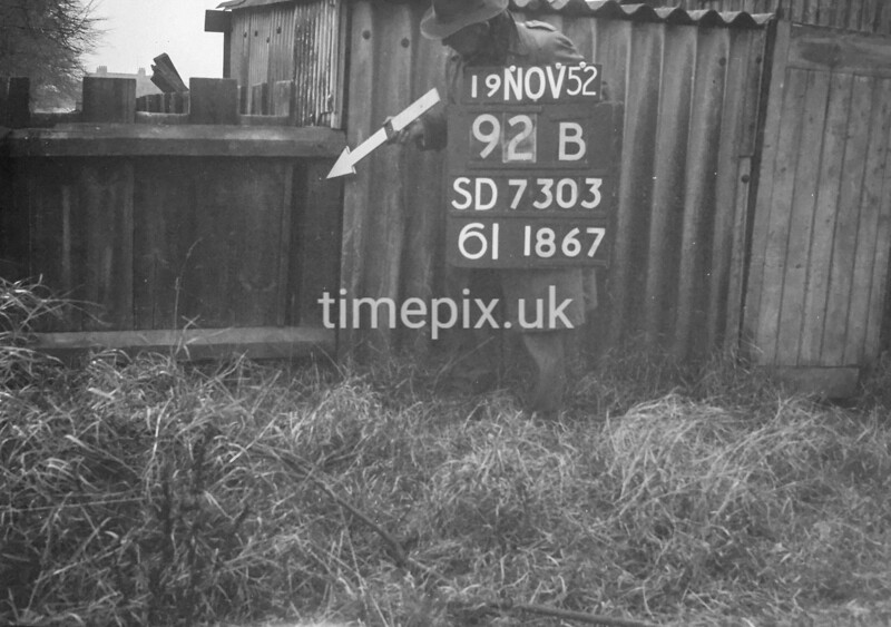 SD730392B, Man marking Ordnance Survey minor control revision point with an arrow in 1950s