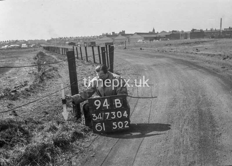 SD730494B, Man marking Ordnance Survey minor control revision point with an arrow in 1940s