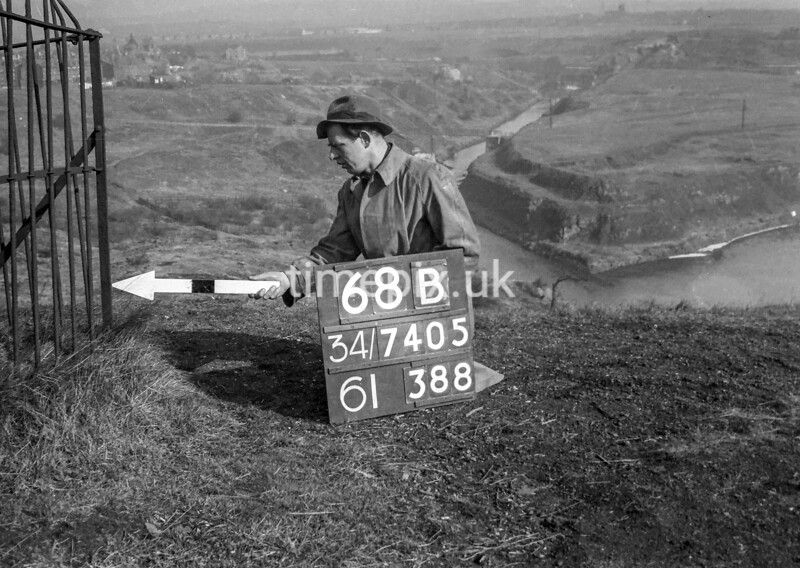 SD740568B, Man marking Ordnance Survey minor control revision point with an arrow in 1940s