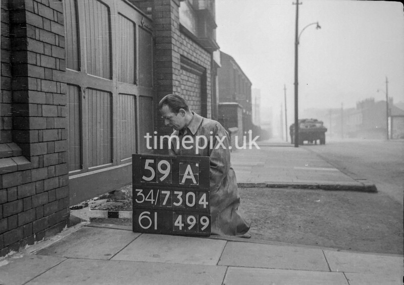 SD730459A, Man marking Ordnance Survey minor control revision point with an arrow in 1940s