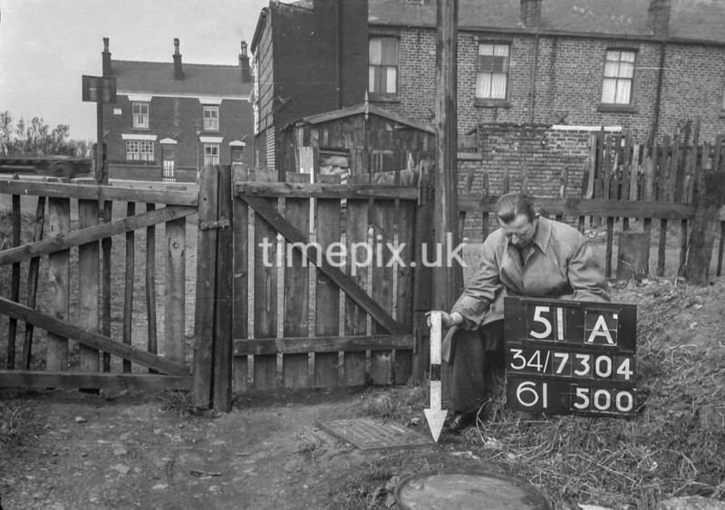 SD730451A, Man marking Ordnance Survey minor control revision point with an arrow in 1940s