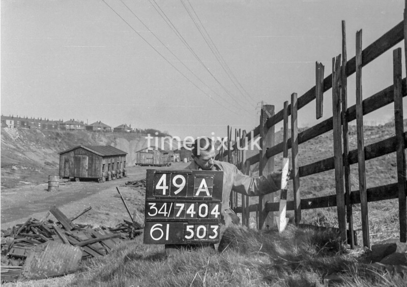 SD740449A, Man marking Ordnance Survey minor control revision point with an arrow in 1940s