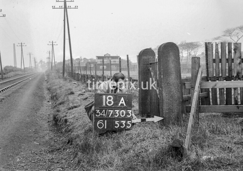 SD730318A, Man marking Ordnance Survey minor control revision point with an arrow in 1940s