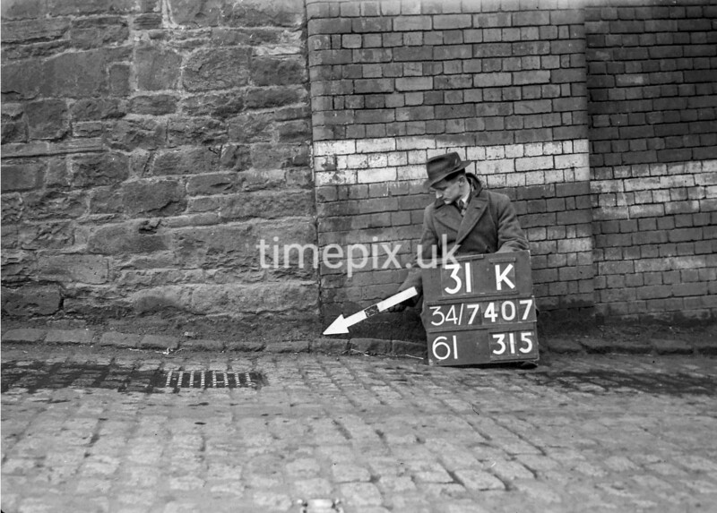 SD740731K, Man marking Ordnance Survey minor control revision point with an arrow in 1940s