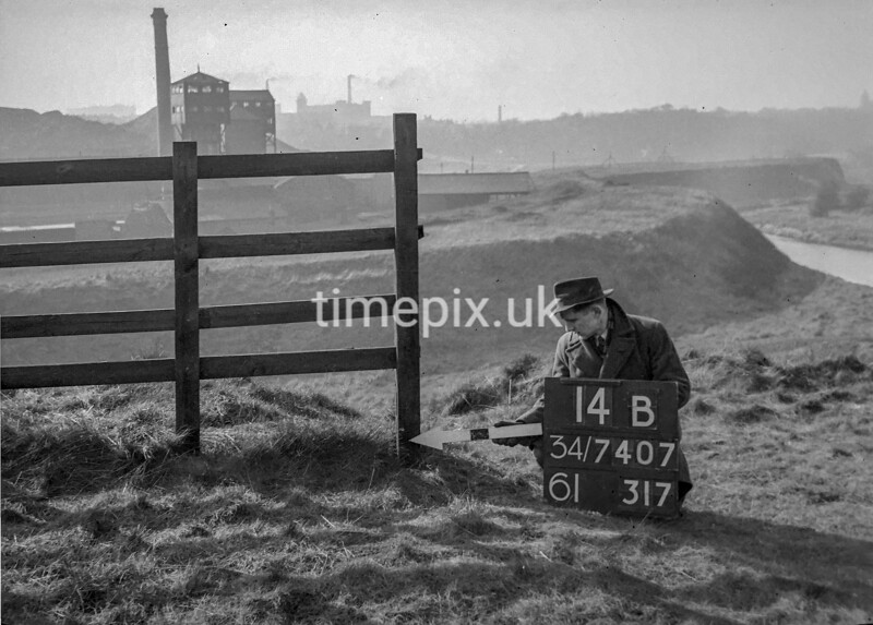 SD740714B1, Man marking Ordnance Survey minor control revision point with an arrow in 1940s