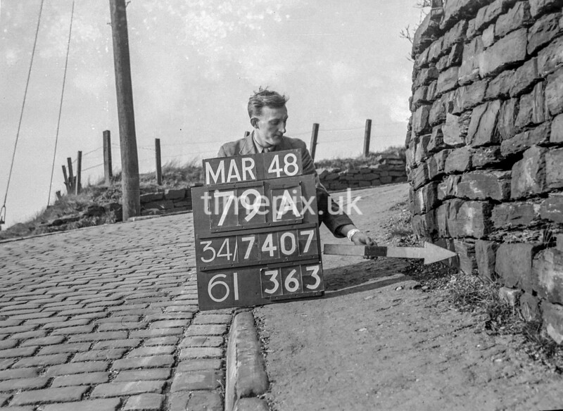 SD740779A, Man marking Ordnance Survey minor control revision point with an arrow in 1940s