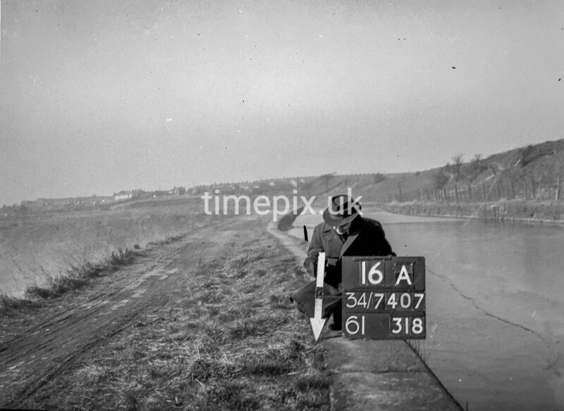 SD740716A, Man marking Ordnance Survey minor control revision point with an arrow in 1940s