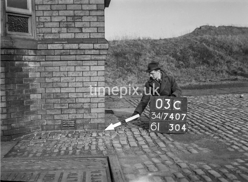 SD740703C, Man marking Ordnance Survey minor control revision point with an arrow in 1940s