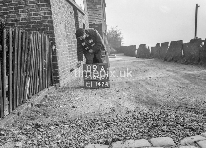 SD740709A, Man marking Ordnance Survey minor control revision point with an arrow in 1940s