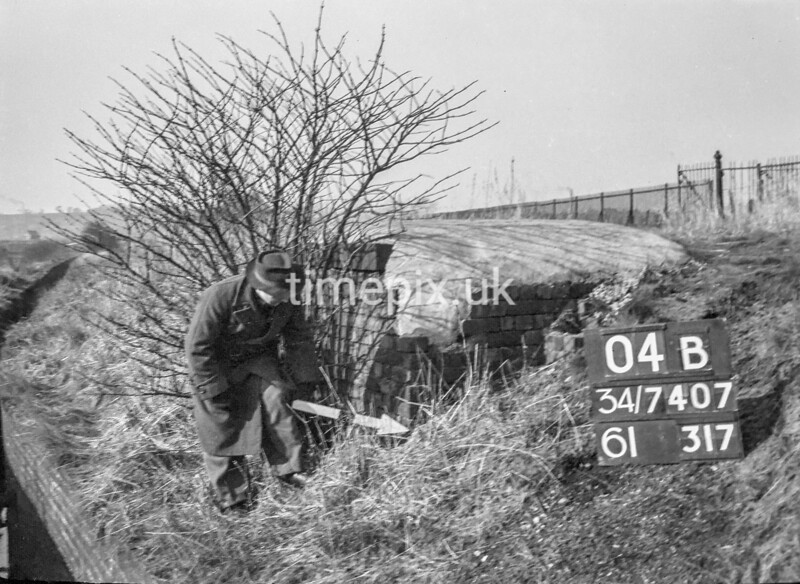 SD740704B, Man marking Ordnance Survey minor control revision point with an arrow in 1940s