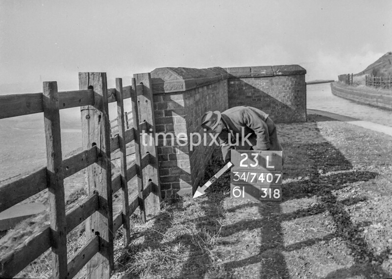 SD740723L, Man marking Ordnance Survey minor control revision point with an arrow in 1940s