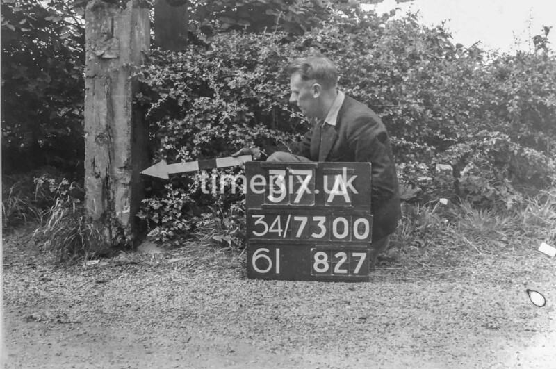 SD730037A, Man marking Ordnance Survey minor control revision point with an arrow in 1940s
