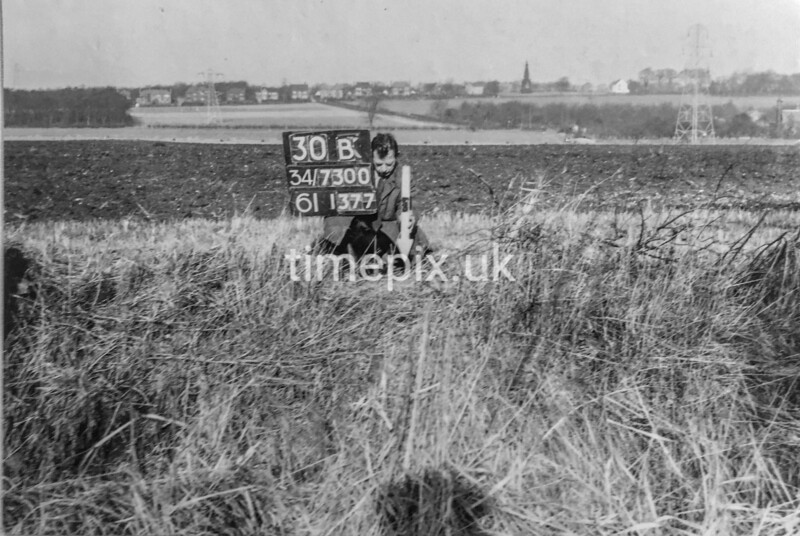 SD730030B, Man marking Ordnance Survey minor control revision point with an arrow in 1950s